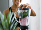 woman blending pink smoothie
